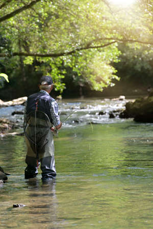 fly fisherman in summer fishing in a mountain river with waders and a cap 스톡 콘텐츠 - 151815046