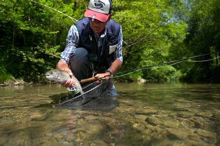 fly fisherman in summer catching a rainbow trout fishing in a mountain river 스톡 콘텐츠 - 151815057