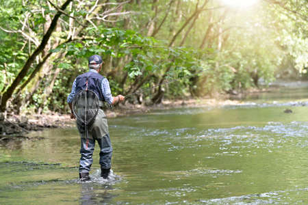 fly fisherman in summer fishing in a mountain river with waders and a cap Stock fotó