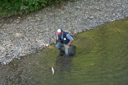 fly fisherman in summer catching a rainbow trout fishing in a mountain river Stock fotó