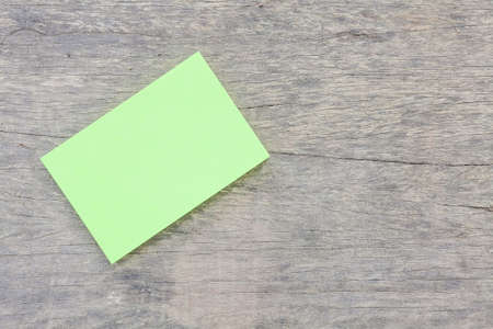 green reminder sticky note on wood plate