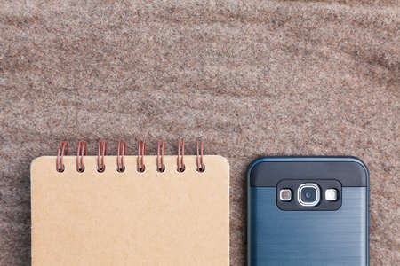 industrious: notebook page and smartphone on brown fabric, upper empty space fot text