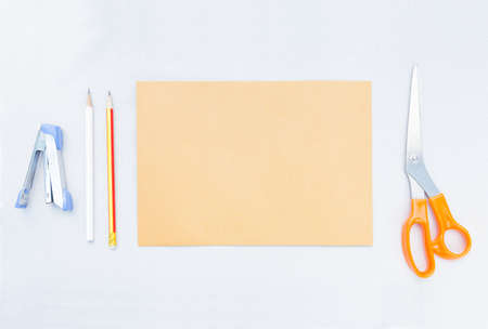 avocation: stapler pencil brown sheet paper and scissors, handcraft tools placed on gray background, leave space for copy