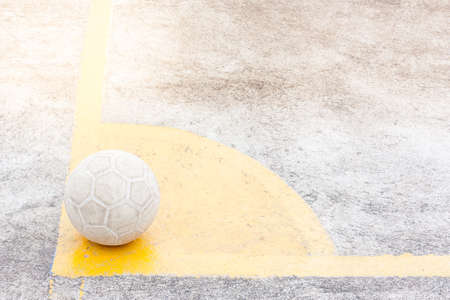 its a ball of soccer or football place on yellow corner, ground is concrete