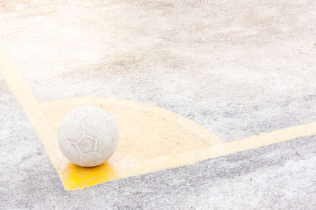 indigent: its a ball of soccer or football place on yellow corner, ground is concrete