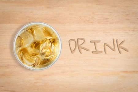 potation: cool drink in glass place at left side wood texture background, drink text water effect at right side of image