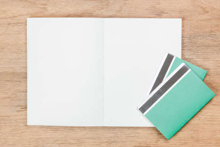 open book and green book bank on brown wood table, financial concept Stock Photo