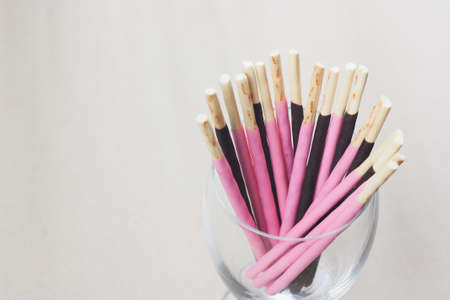 Chocolate, pink biscuits sticks in glass, its a sweet snack, empty gap left side for copy space Stock Photo