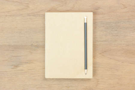 close brown book and black pencil on brown wood table