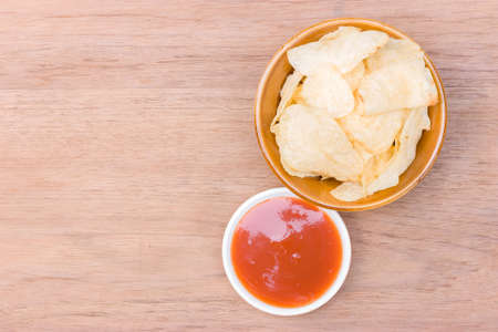 potato chips on bowl and catchup place on right side of wood table Stock Photo