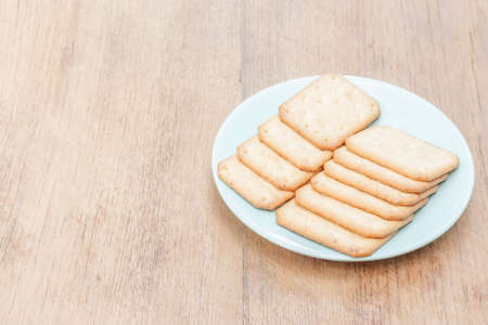 biscuits dish placed on the right side of brown wood table
