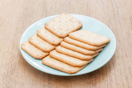 biscuits in green plate on brown wood table