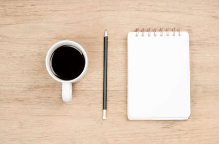 white coffee cup, black pencil and opened notebook place on wood texture, break time or thinking time concept, from top view
