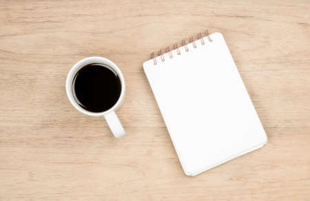 white opened notebook and white coffee cup place on brown wood texture,  from top view