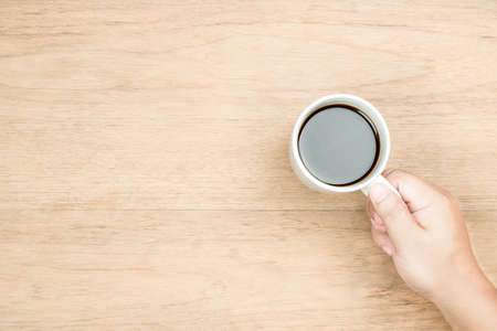yellow brown hand hold white coffee cup on wood texture, from top view, right hand side,  empty area for copy space