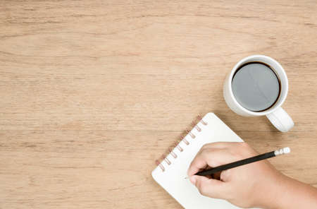 brown skin hand use black pencil writing on white page of small notebook and white coffee cup place on wood texture, empty area on left of image for copy space and thinking time concept, from top view