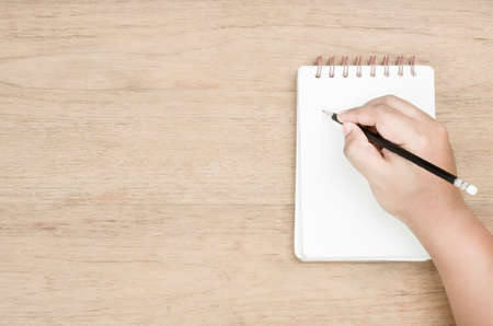 brown skin hand use black pencil writing on white page of small notebook place on wood texture, empty area on left of image for copy space and thinking time concept, from top view Stock Photo