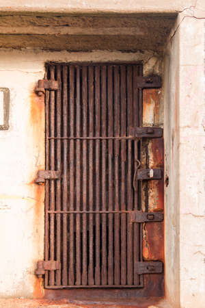 metal grate: Old rusty door in the form of a thick metal grate Stock Photo