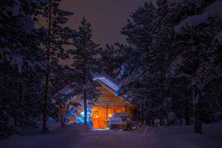cottage: Winter windless night. Dense spruce forest. Wooden house lighted and a lot of snow. Car and snowmobile are there