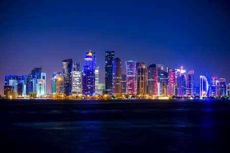 Катар. Доха-небоскребы с наружным освещением. Безоблачное небо и ночь Редакционное