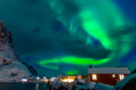 Winter Norway. Lofoten. Hamnoya town. Aurora Borealis above the roofs of houses Banco de Imagens