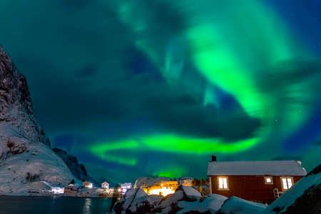 Winter Norway. Lofoten. Hamnoya town. Aurora Borealis above the roofs of houses Standard-Bild