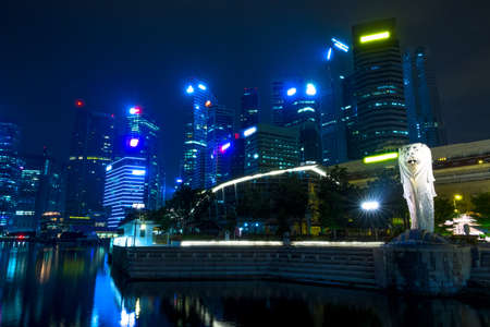 Singapore at night. Downtown with Merlion and skyscrapers Editorial