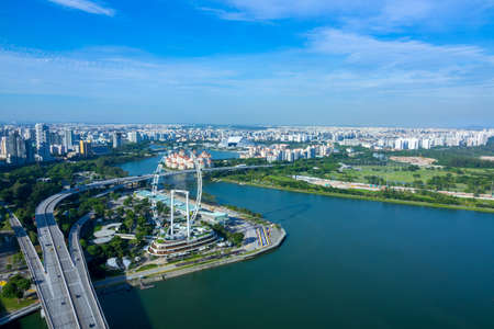 Singapore. Sunny day. Panorama of residential areas, Ferris wheel and highway. Aerial view Editorial