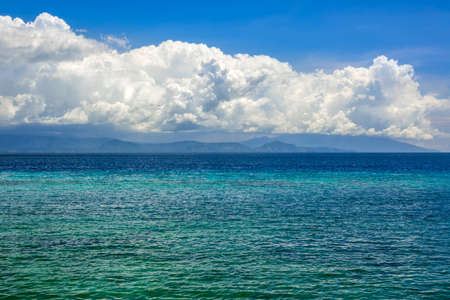 Indonesia. Sunny day. Turquoise water of a calm ocean. Surprisingly beautiful clouds over a distant island Фото со стока