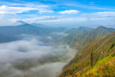 Indonesia. Java island. Morning in the Bromo Tengger Semeru National Park. Dense fog in the valley between volcanoes