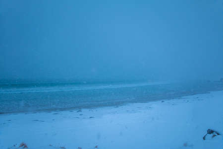 Winter beach. Heavy snowfall hides the horizon. Minimum visibility Banco de Imagens
