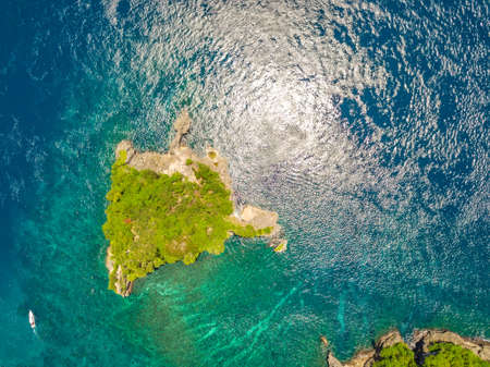 Indonesia. Little rocky desert island, overgrown with jungle. Motorboat near. Aerial view