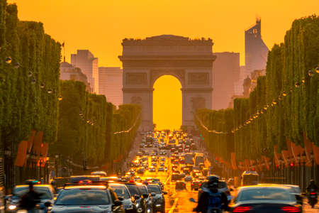 France. Paris. Dense traffic on the Champs Elysees. Triumphal Arch on a background of golden sunset