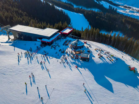 Ski resort in sunny weather. Snow on the ski slope of a wooded mountain. Many tourists near the ski lift station and cafe. Aerial View Stock Photo