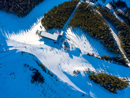 Ski resort in sunny weather. Ski slope of a wooded mountain. Many tourists near the ski lift station and cafe. Aerial View