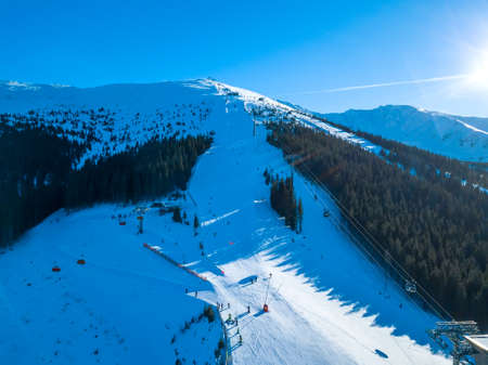 Ski resort in sunny weather. Ski slopes of a wooded mountain. Many tourists. Aerial View Stock Photo