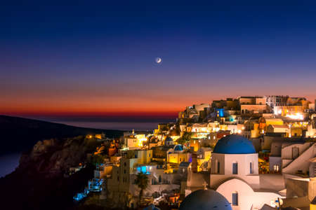 Greece. Thira Island. Nidght roofs of Oia at the late evening and moon