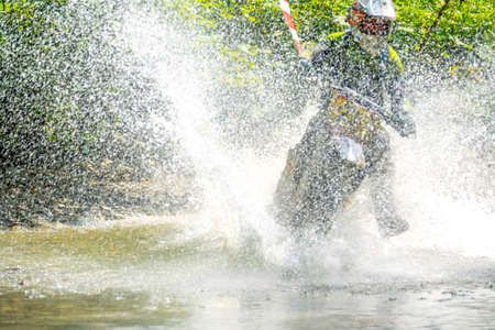 Summer sunny day in the forest. Enduro athlete overcomes a shallow stream with lots of splashes