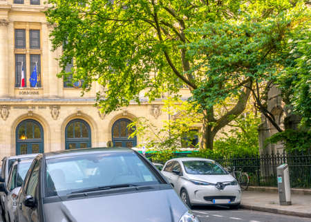 France. Summer sunny day in Paris. Green garden near the University of Sorbonne. Several cars are parked on a narrow street. Electric car connected to a charger