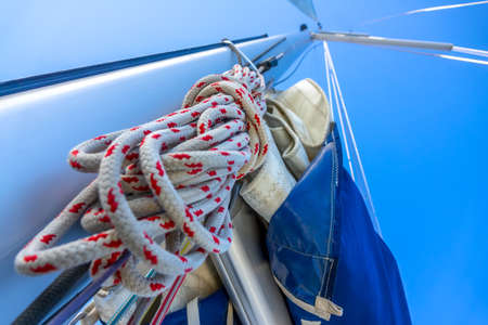 Blue sky. Bottom view of the mast of a sailing yacht. A hank of rope and other rigging