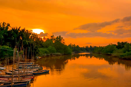 River in the rainforest at sunset. Several boats off the coast Banco de Imagens