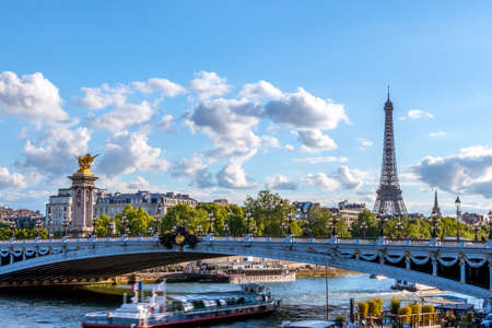 France. Sunny summer day in Paris. Pleasure boat under the bridge of Alexander III over the river Seine. Eiffel Tower Stock Photo