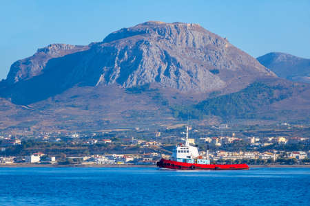 Sunny summer day in the gulf of Corinth. View from the water to the tugboat in the background of a small town on a mountainous shore