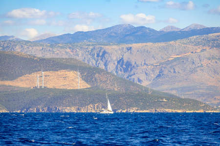 Lonely sailing yacht at sunny summer day and the hilly coast with wind farms