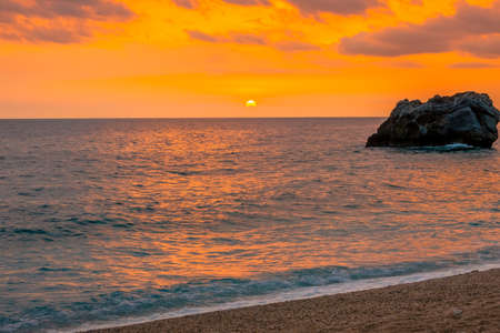 Multicolor sunrise over calm water. Strip of sandy beach on the Greek coast of the Mediterranean sea