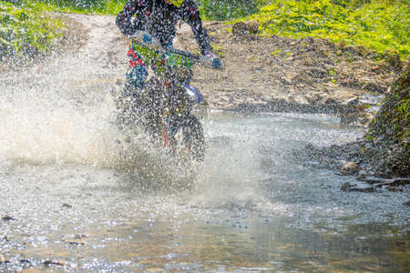 Sunny summer day and forest streem. A lot of splash of water hides an enduro motorcycle