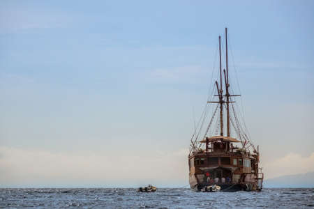 Large sailing ship with scuba divers anchored in the ocean. Two inflatable motor boats on a leash