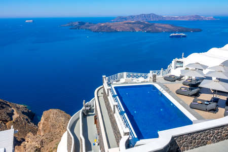 Greece. Thira island. Santorini. Hotel on the high bank in Oia. Pool and sun loungers for relaxation in sunny weather. Seascape 報道画像