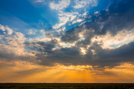 Summer steppe plain. Colorful sunset with many illuminated clouds Stock Photo