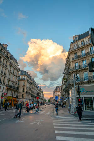France. Summer day on an old street in Paris. Color cloud in blue sky